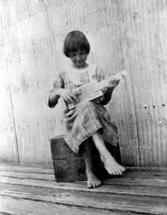 Barefoot girl sitting on a box playing a cigar box banjo
