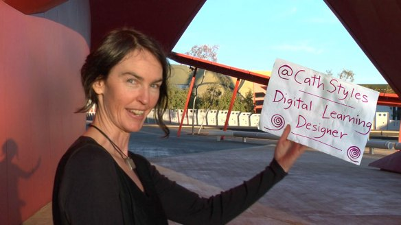 Cath Styles at the entrance to the National Museum of Australia, with a sign Photoshopped into her hand