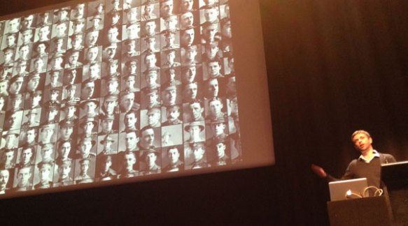 Chris McDowall presenting on a large screen his clusters of algorithmically-cropped faces of WWI soldiers