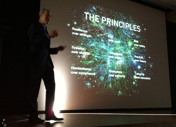 Glenn Lowry in front of a screen displaying a set of principles for the network age
