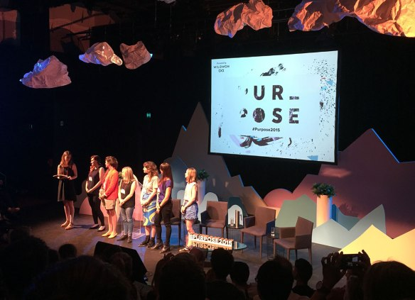 Seven young women on a stage before a crowd of people. The screen says 'Purpose / #purpose2015' and the staging includes mountains, waves and clouds.